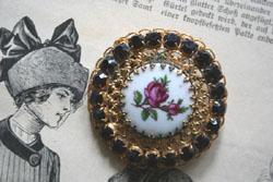 Antike Brosche mit Porzellanrose und granatfarbenem Strass